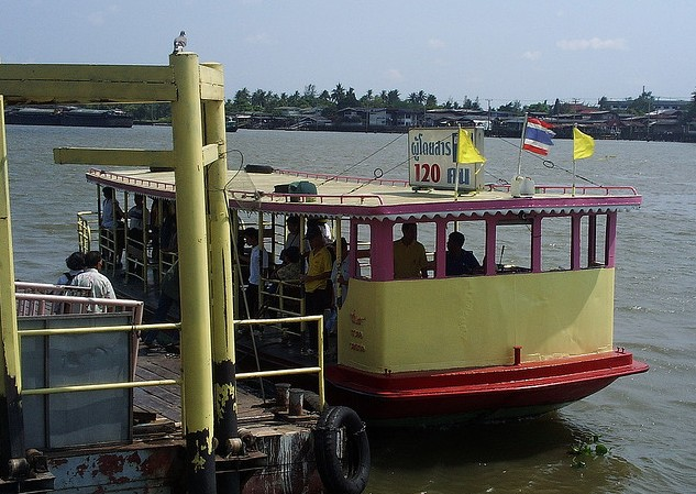 A cross river ferry at its pier while passengers are boarding